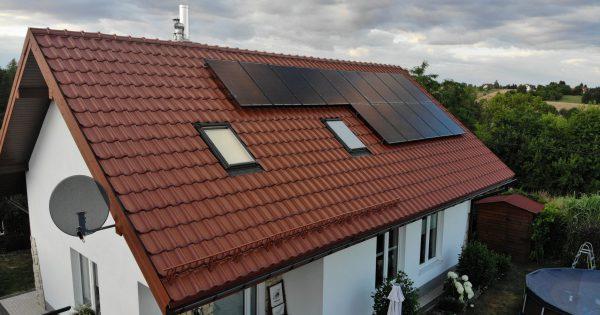 dach budynku z czarnymi panelami słonecznymi
