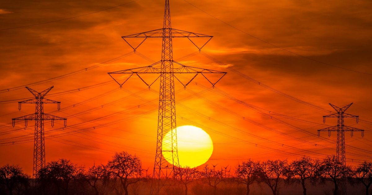 słupy wysokiego napięcia na tle zachodzącego słońca